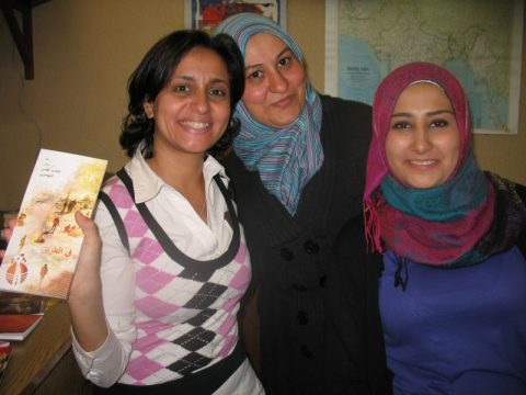 Three women with booklet for refugees